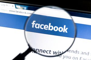 Ostersund, Sweden - August 1, 2015: Facebook website under a magnifying glass. Facebook is the most visited social network in the world