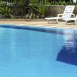Blue water pool and sunloungers on poolside