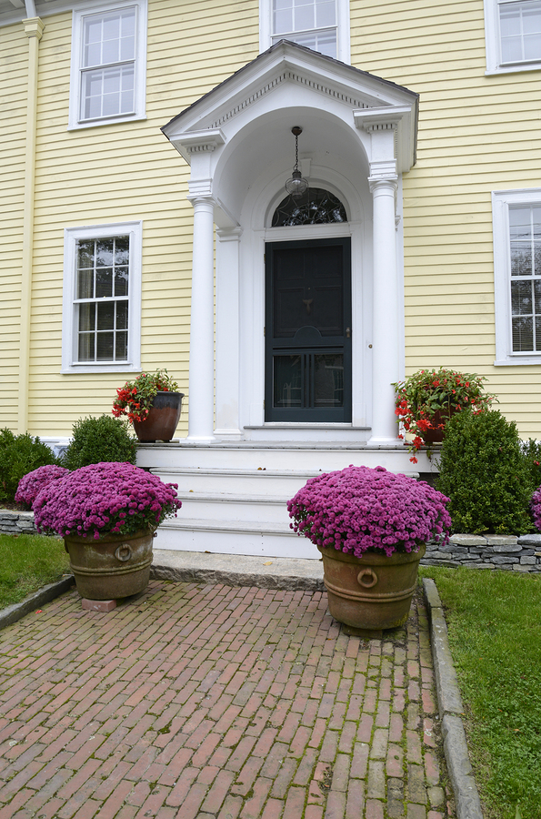 yellow multi-story house with a portico brick sidewalk and flowers with pink flowers