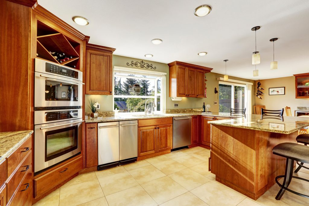 Luxury kitchen with tile floor stained cabinets and granite counter top