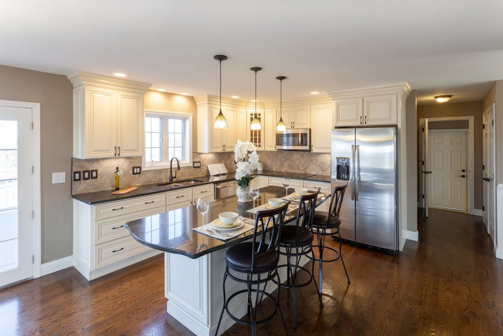 Beautiful staged kitchen room in a modern house with granite countertops and antique finished cabinets.