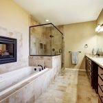 Master bathroom in modern house with fireplace bath tub with tile trim glass shower and modern cabinets.