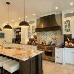 Focal point of the Kitchen is the Wolf 6 burner range with a custom metal hood and Ann Sacks - Beau Monde Glass tile.