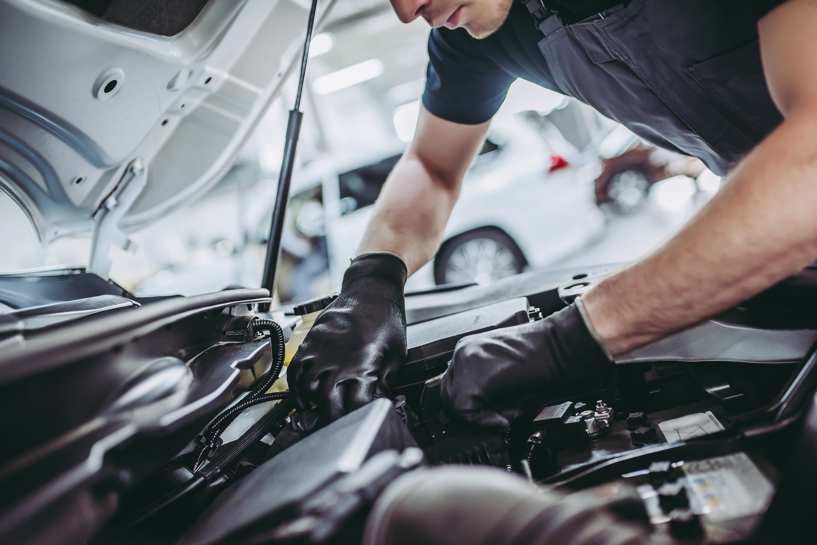 Cropped image of handsome mechanic in uniform is working in auto service. Car repair and maintenance.