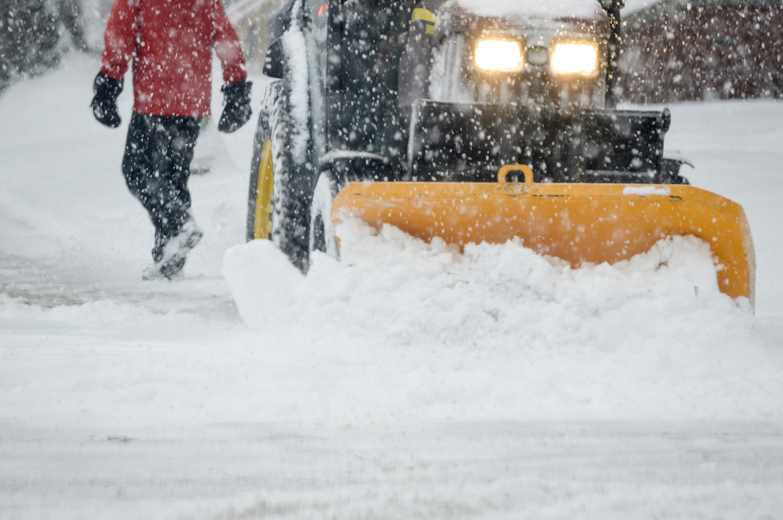 Winter storm conditions with snow removal on city streets with snow plow plowing the roads and pedestrian person walking through snow storm in icy winter weather background image