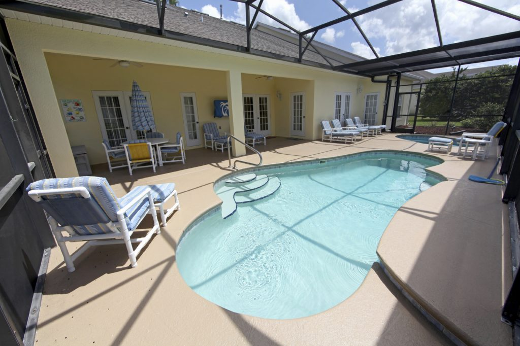 A Swimming Pool, Spa and Lanai with chairs