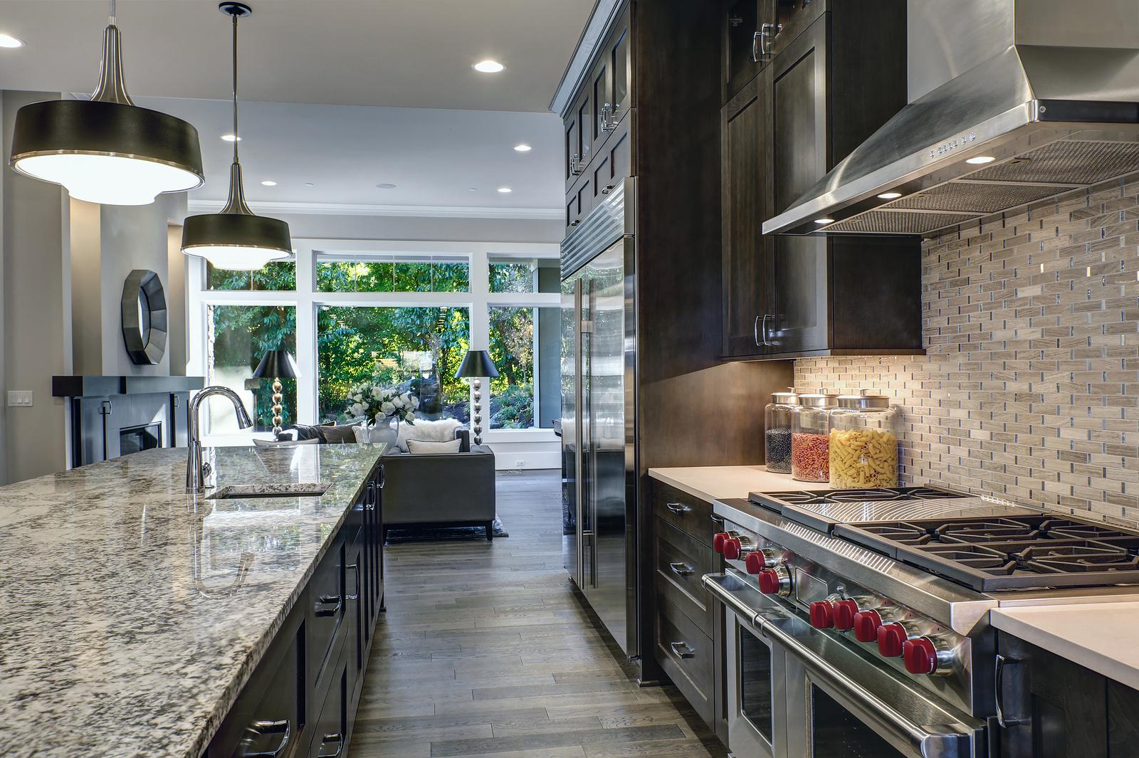 Modern kitchen with brown kitchen cabinets, oversized kitchen island with bar stools, granite countertops, huge refrigerator and beige backsplash. Northwest, USA
