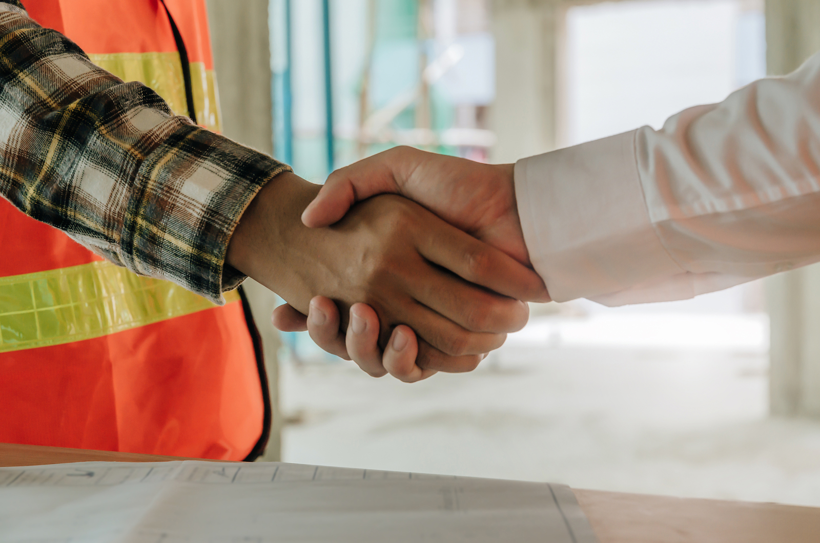 construction worker team contractor hand shake after finishing up a business meeting to greeting start up project contract in construction site building, teamwork, partnership and industry concept